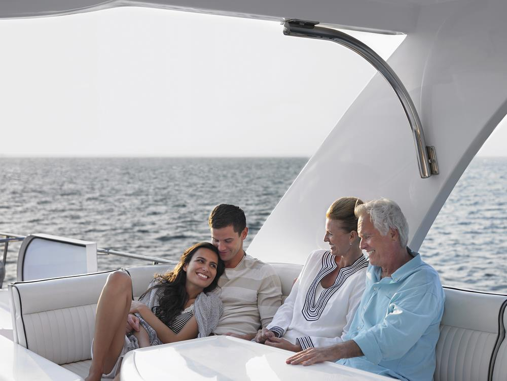 Older and younger couples enjoying yachting together